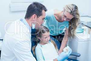 Dentist with assistant teaching girl how to brush teeth