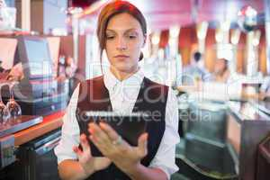 Focused barmaid using touchscreen till