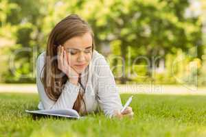 University student lying and writing on notepad