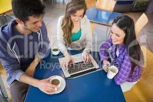 Young students doing assignment on laptop together
