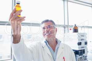 Smiling scientist in lab coat holding a chemical bottle