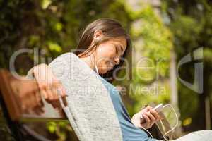 Smiling student sitting on bench text message on her mobile phon