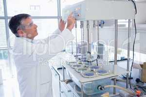Scientist with safety glasses using the machine