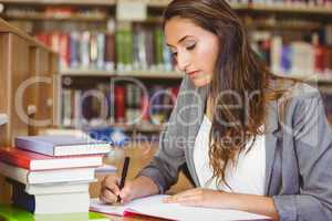 Concentrating brunette student doing her assignment