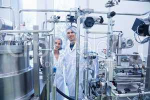 Scientist team behind metal gauge looking at camera