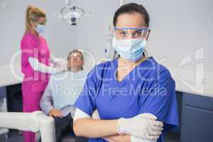 Dentist wearing surgical mask and safety glasses arms crossed