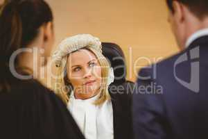 Judge and lawyer listening the criminal in handcuffs