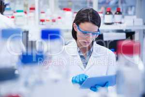 Chemist wearing safety glasses and using tablet pc