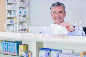 Pharmacist with grey hair holding a prescription