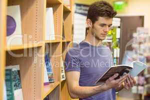 University student standing reading textbook