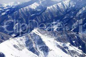 Top view on snowy mountains with forest
