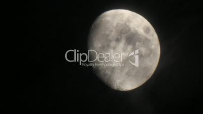 Bright moon disk through night dark veil clouds