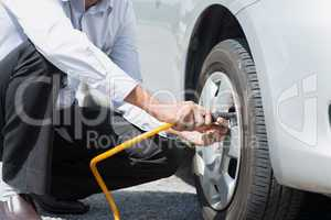 Filling air to the car tires.