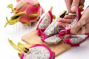 Hands Removing Pulp From A Pitaya Fruit Wedge