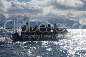 Backlit Zodiac crew speeding past Arctic mountains