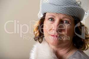 Close-up of brunette in blue veiled hat