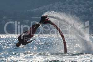 Flyboarder diving diagonally headfirst into backlit waves