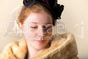 Redhead in black veiled hat and fur coat looking down