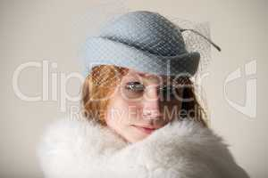Redhead smiling in blue veiled hat and fur
