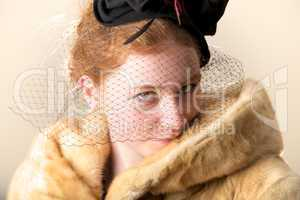 Redhead smiling shyly in black veiled hat and fur coat