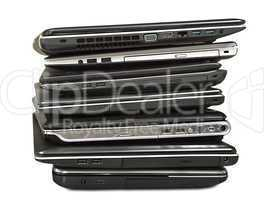 stack of old laptops awaiting repair isolated on white backgroun