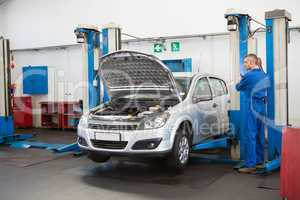 Mechanic raising the car with a workshop jack