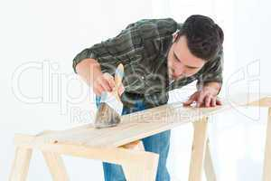Worker using brush on wooden plank