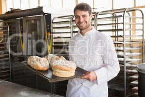 Happy baker showing tray with bread