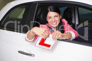 Cheerful female driver tearing up her L sign