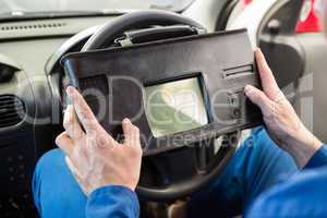 Mechanic using diagnostic tool in the car
