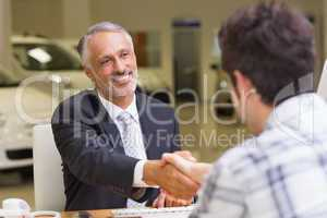 Smiling salesman shaking a customer hand