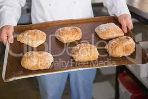 Close up of baker showing tray with bread