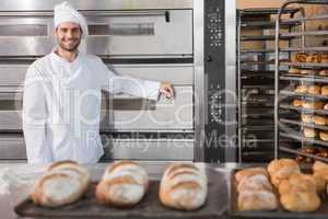 Happy baker leaning on professional oven