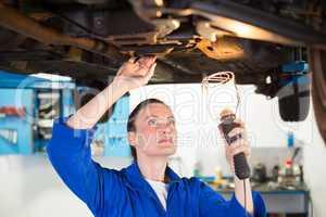 Mechanic shining torch under car
