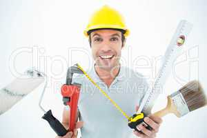 Portrait of happy worker holding various equipment