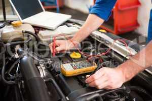 Mechanic using diagnostic tool on engine
