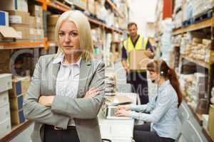 Serious warehouse manager standing arms crossed