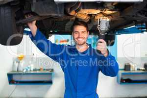 Mechanic using torch to look under car