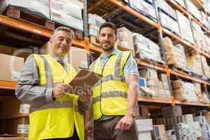 Warehouse manager and foreman looking at camera