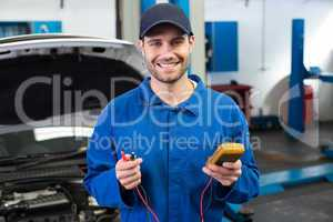 Mechanic smiling at the camera holding tool