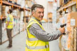 Warehouse worker scanning barcode on box