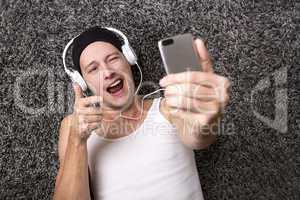 Attractive man with headphones makes selfie with his mobile