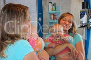 happy mother with her little daughter in front of mirror