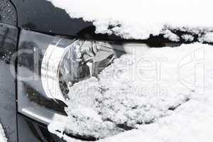 Snowed car headlights in winter