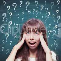Young girl with questioning expression and question marks