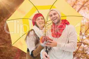 Composite image of autumn couple holding umbrella