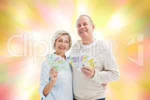 Composite image of happy mature couple smiling at camera showing