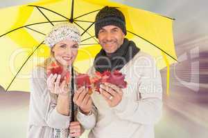 Composite image of couple in winter fashion showing autumn leave