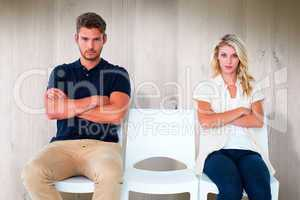 Composite image of young couple sitting in chairs not talking du