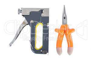 pliers and staple gun in hand on a white background